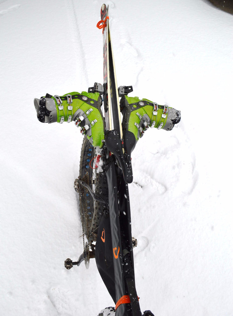 Close up of skis and boots attached to a bike with the Gunslinger Ski Carry