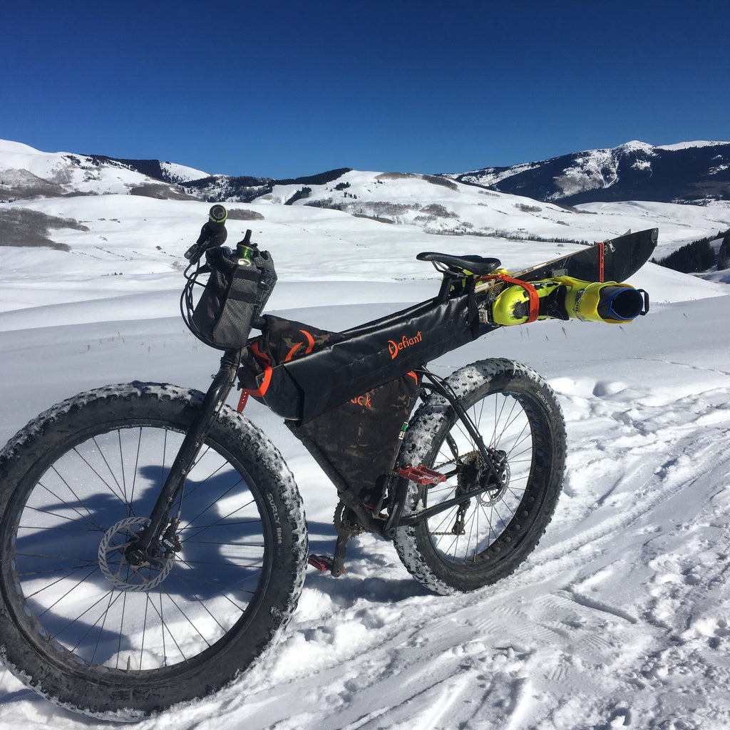 Surly Pugsley with black Defiant Pack custom framebag and Gunslinger Ski Carry with skis and boots attached in Crested Butte Colorado