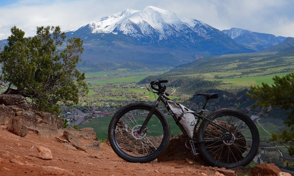 Defiant Pack custom zipperless frame bag on bicycle with view of Mt Sopris from mushroom rock