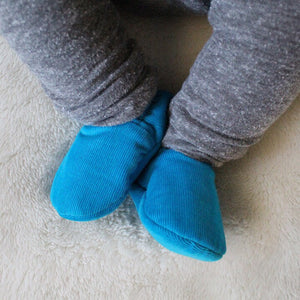 Baby boy wearing Bright Turquoise Loafie Brights baby slippers
