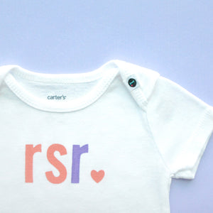 Monogrammed baby onesie with coral and lavender letters