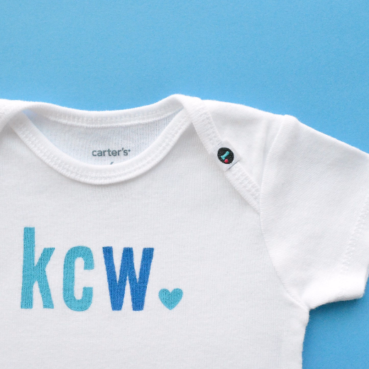 Monogrammed baby onesie with turquoise and blue letters