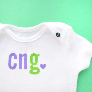 Monogrammed baby onesie with purple and green letters