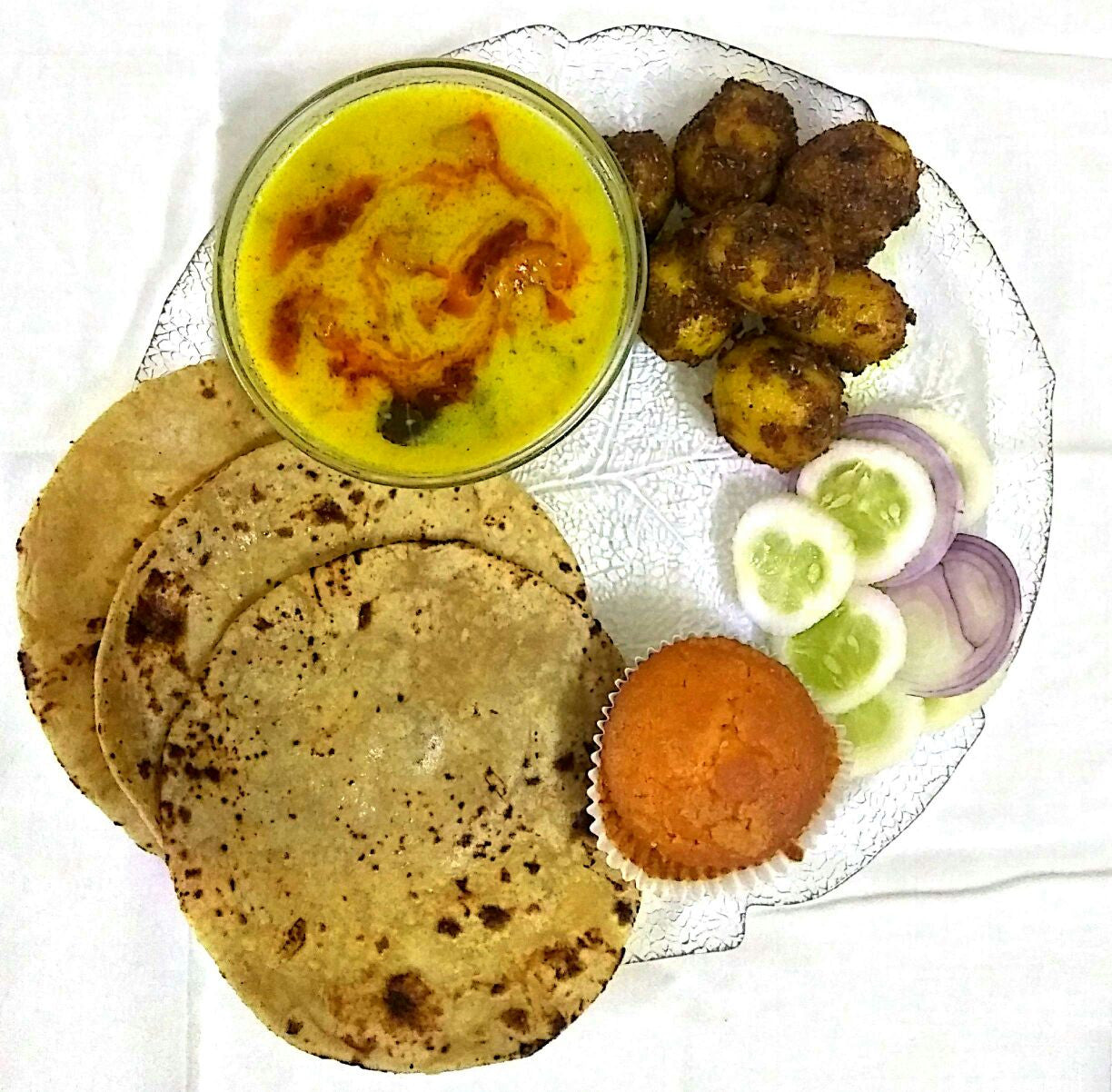 Rajasthani Gatta Curry, Dum Aloo Masaledar with Butter Roti (3 Pieces), Salad & Veg Muffin