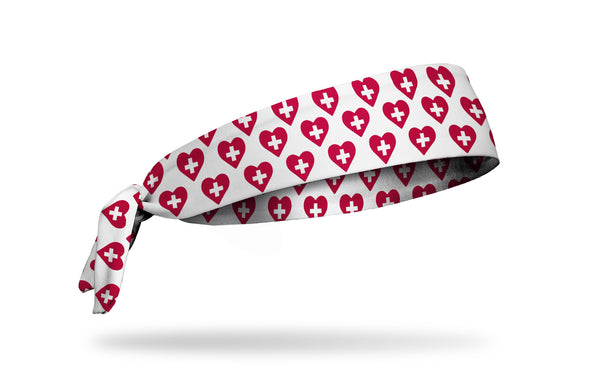 white medical themed headband with white positive symbol inside red heart pattern