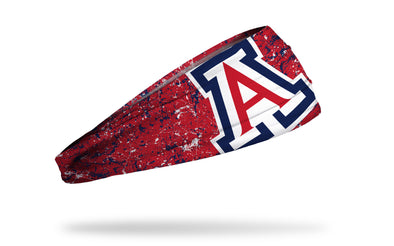 red headband with navy and white paint splatter and oversize University of Arizona A logo