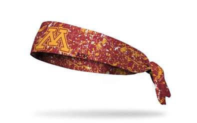 maroon headband with gold paint splatter and University of Minnesota M logo in gold