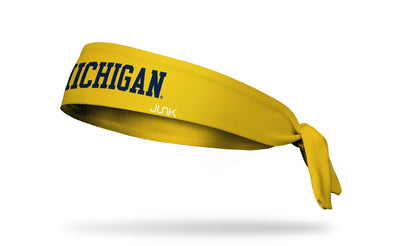 gold headband with University of Michigan Michigan wordmark logo in navy