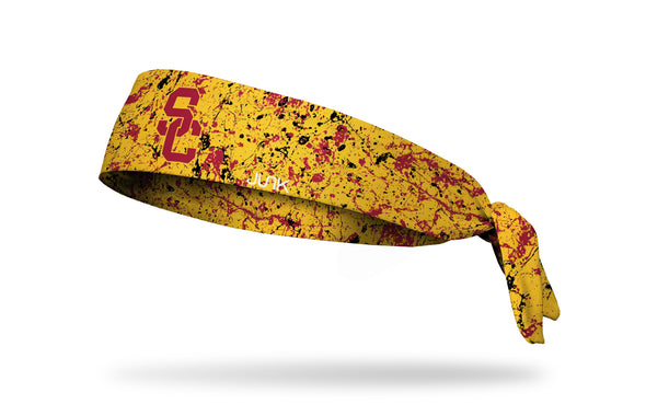 gold headband with paint splatter design and University of Southern California logo