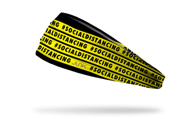 black headband with yellow warning tape that repeating says hashtag social distancing