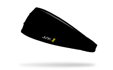 left side view of all black big bang lite headband with yellow ribbon to right of JUNK logo