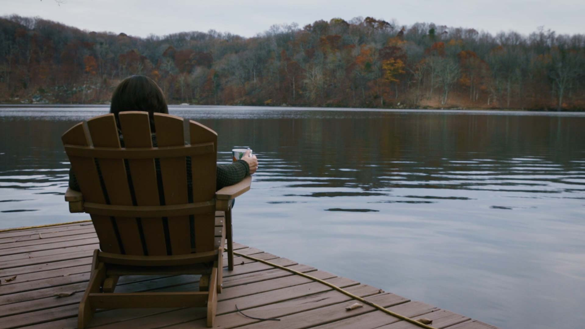 A woman wearing Elimindi apparel sitting out on a lake with a cup in her hand