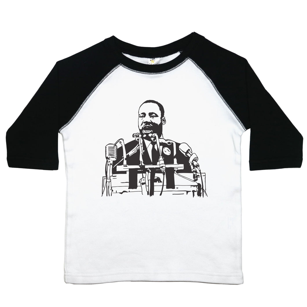 A toddler raglan or baseball style tee with an image of Martin Luther King Jr. in the middle. The 3/4 sleeves are the first color listed with the second color in the middle