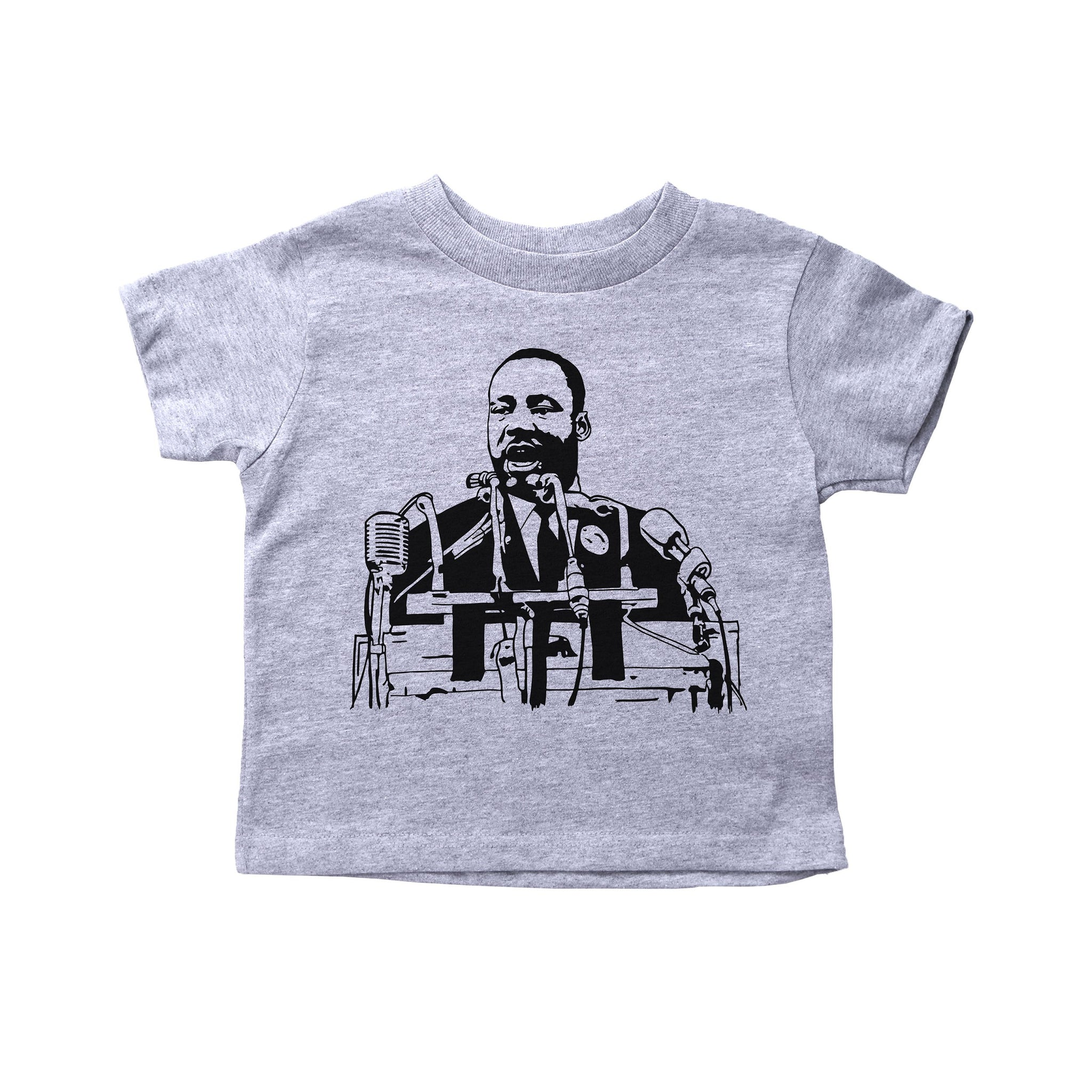 "A short sleeve toddler shirt with Martin Luther King in the middle giving his ""I Have a Dream"" speech surrounded by microphones"
