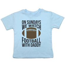 Load image into Gallery viewer, a short sleeved crewneck t-shirt for toddlers that says 'on sundays we watch football with daddy' with a brown football in the center
