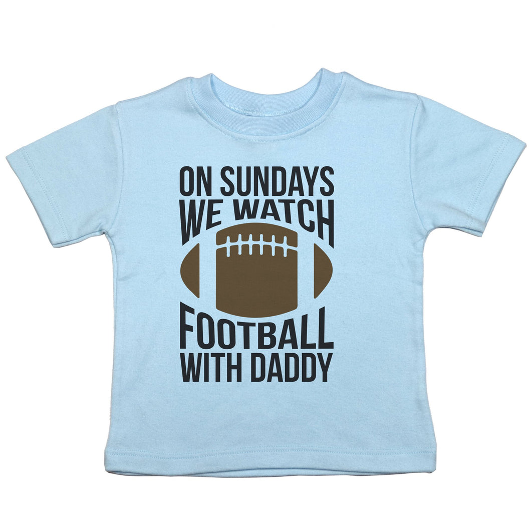 a short sleeved crewneck t-shirt for toddlers that says 'on sundays we watch football with daddy' with a brown football in the center
