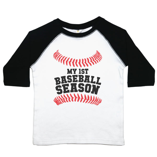 "A toddler raglan or baseball style tee with the words ""My 1st Baseball Season"" with baseball stitching above and below the text. The 3/4 sleeves are the first color listed with the second color in the middle"
