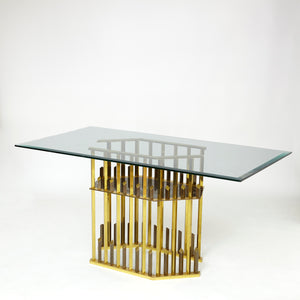 Geometric gold table base of superb quality with glass top .