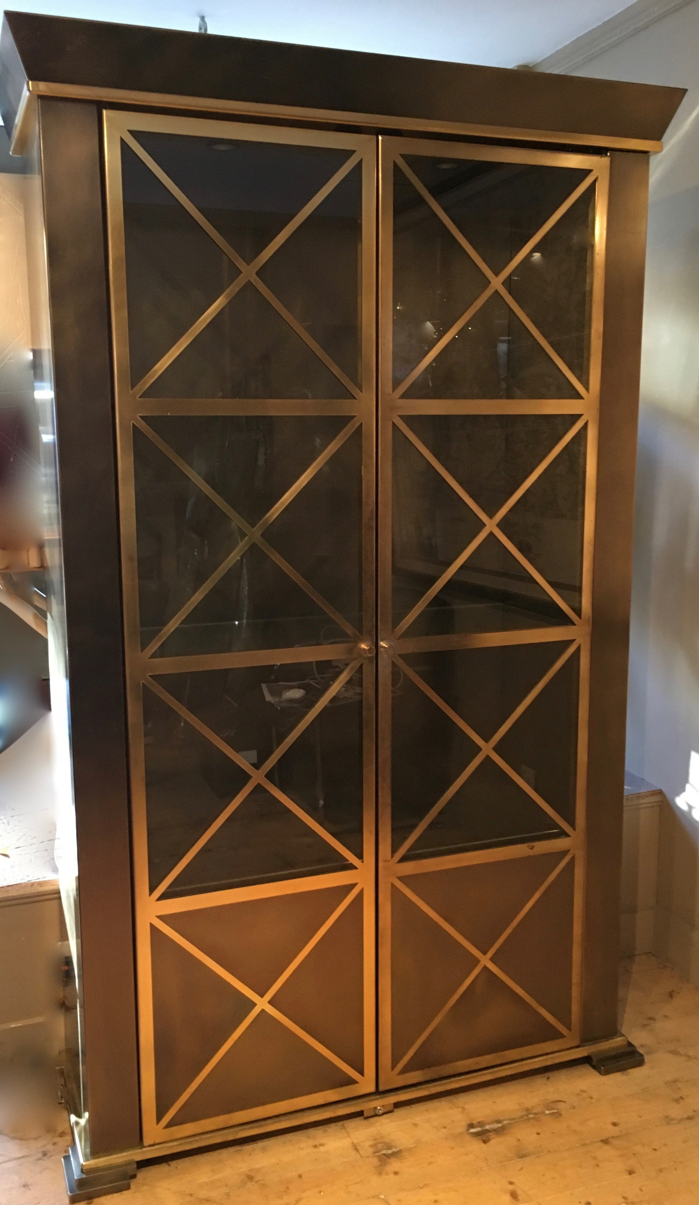 Stunning steel and brass cabinet with neo classical door details circa 1970 .