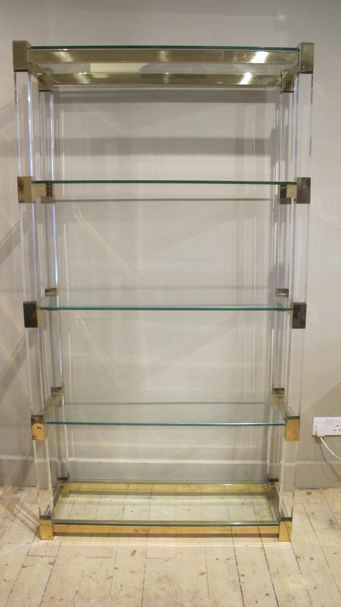 X An impressive perspex shelving unit with 50 mm perspex uprights and heavy gauge bronze frame .