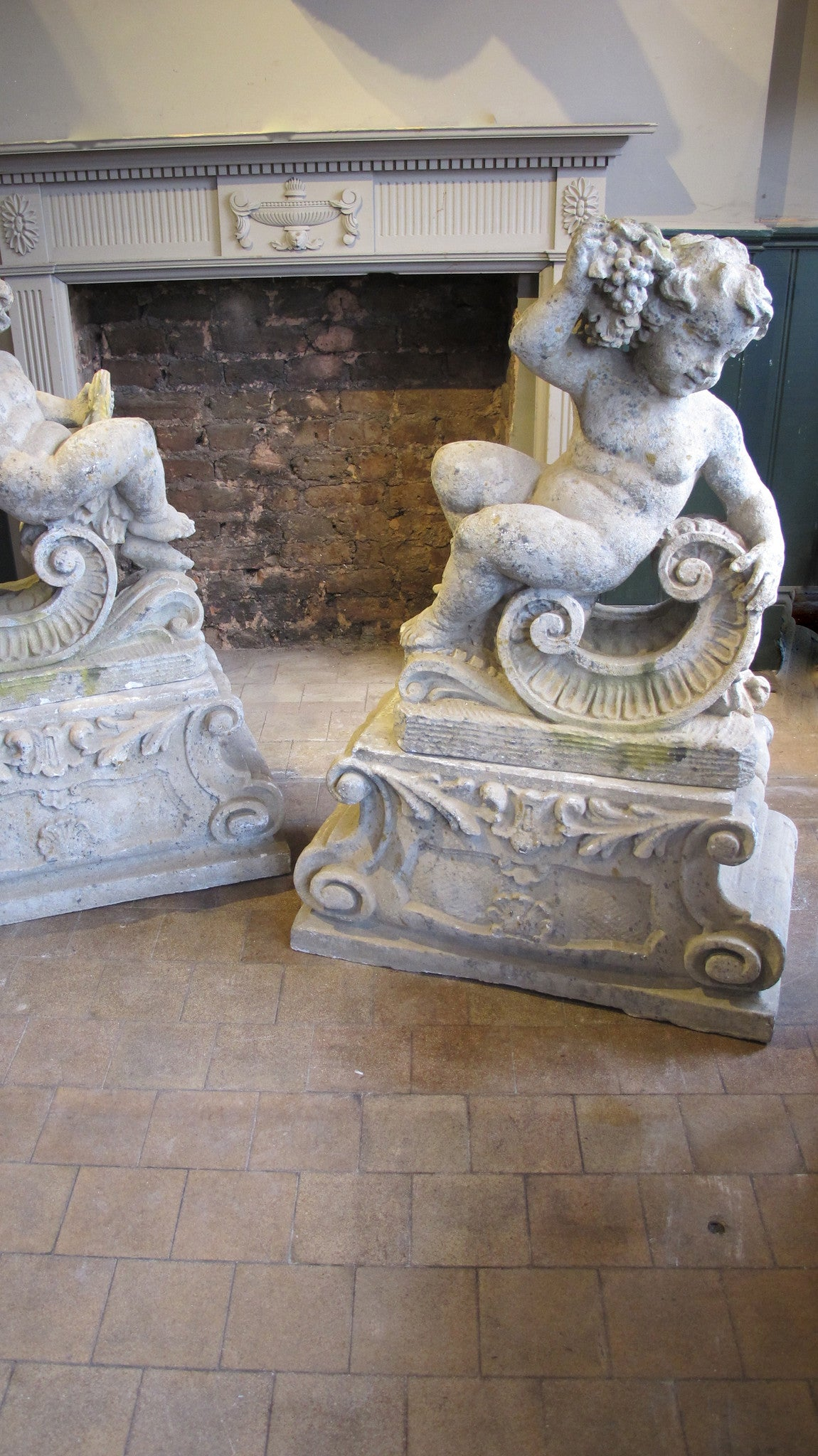 X Pair of Classical reconstituted stone statues of recumbent cherubs early 20th century.