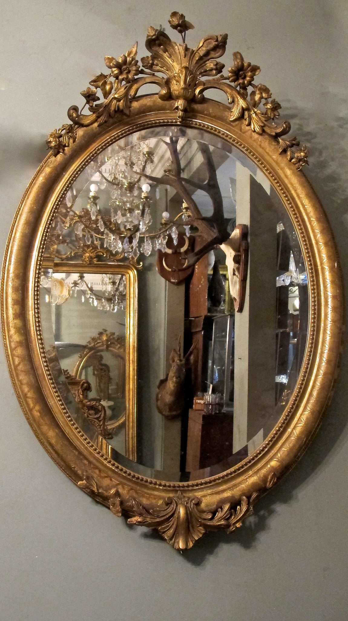 X A pretty gilt oval french mirror  with decorative crest.