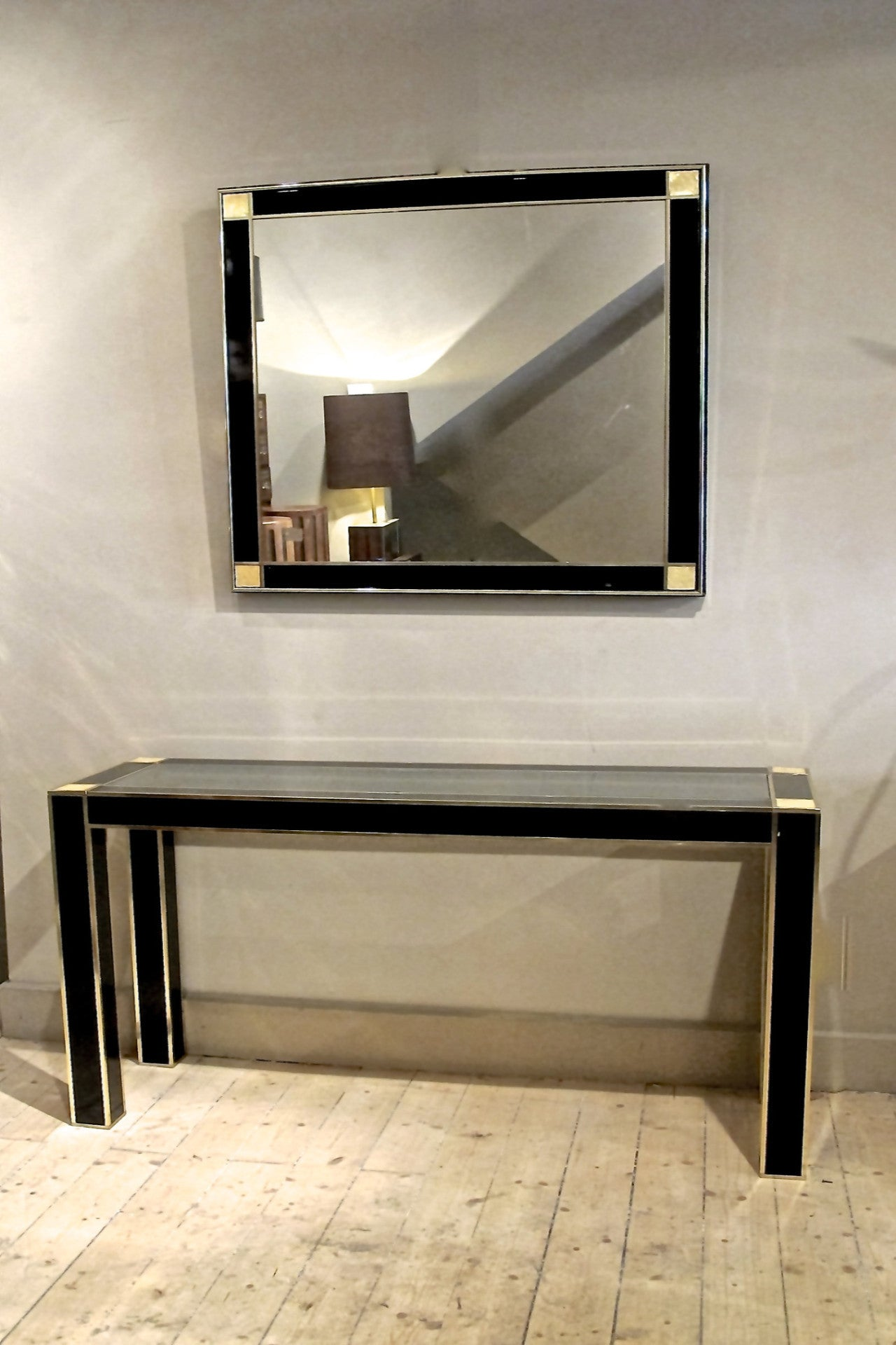 A superb quality black lacquer console and mirror with solid brass trim and mother of pearl corner details.