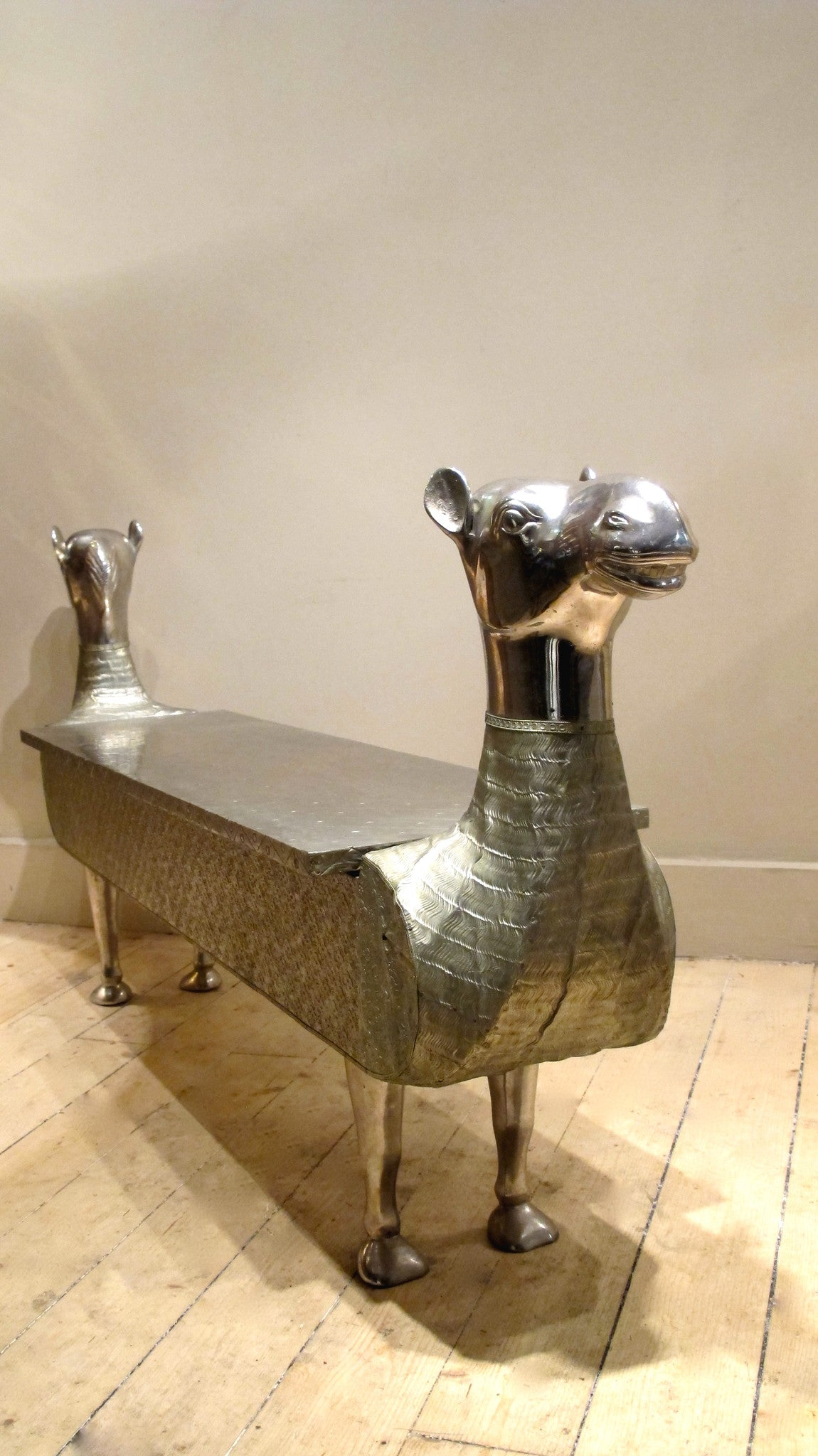 X A fabulous silvered hall bench modelled as a camel with lift up lid and internal storage.Last quarter 20th c.