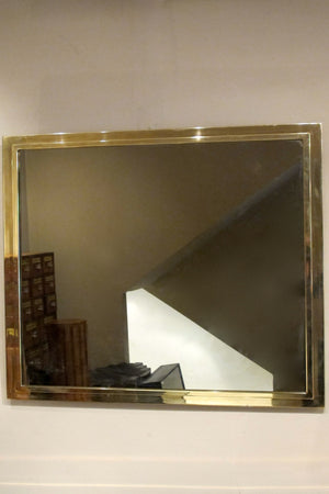 A large 1970s brass mirror with stepped edge detail.