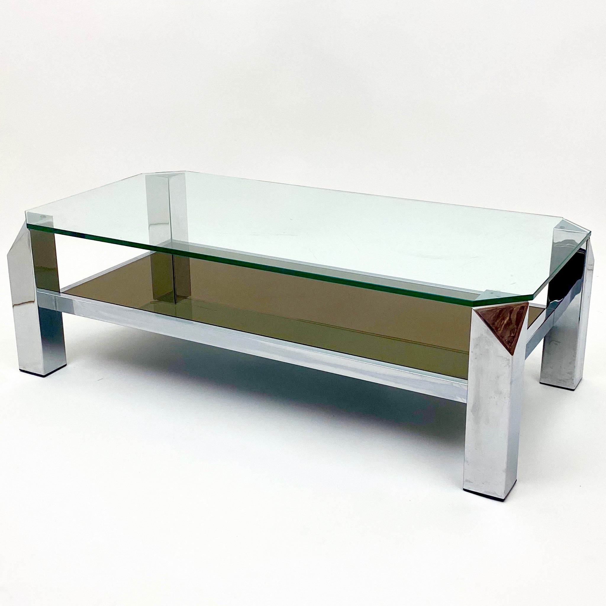 Vintage modernist 2 tier chrome coffee table with canted corners .