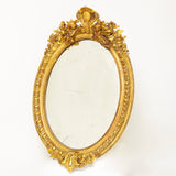 Early victorian oval mirror with original antique gilding .