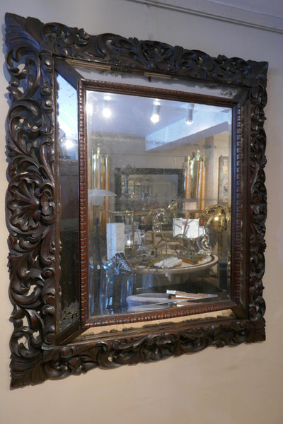 Large carved french mirror of cushioned design with antique mirror . Late 19th century.