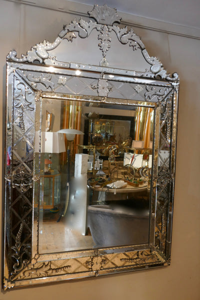 Gigantic Venetian mirror with cushioned border and decorative crest .
