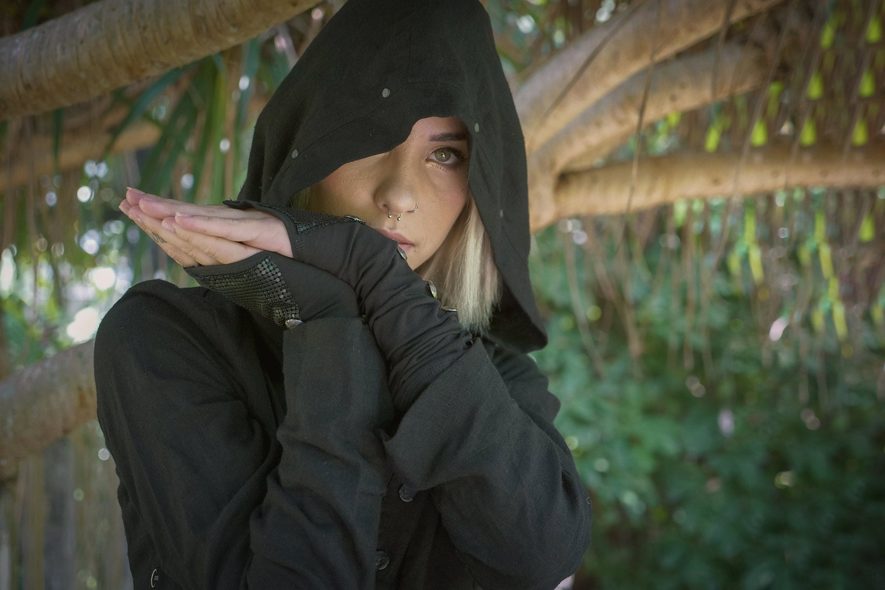 woman against a tree wearing Psylo Fashion streetwear hoodie and long gloves