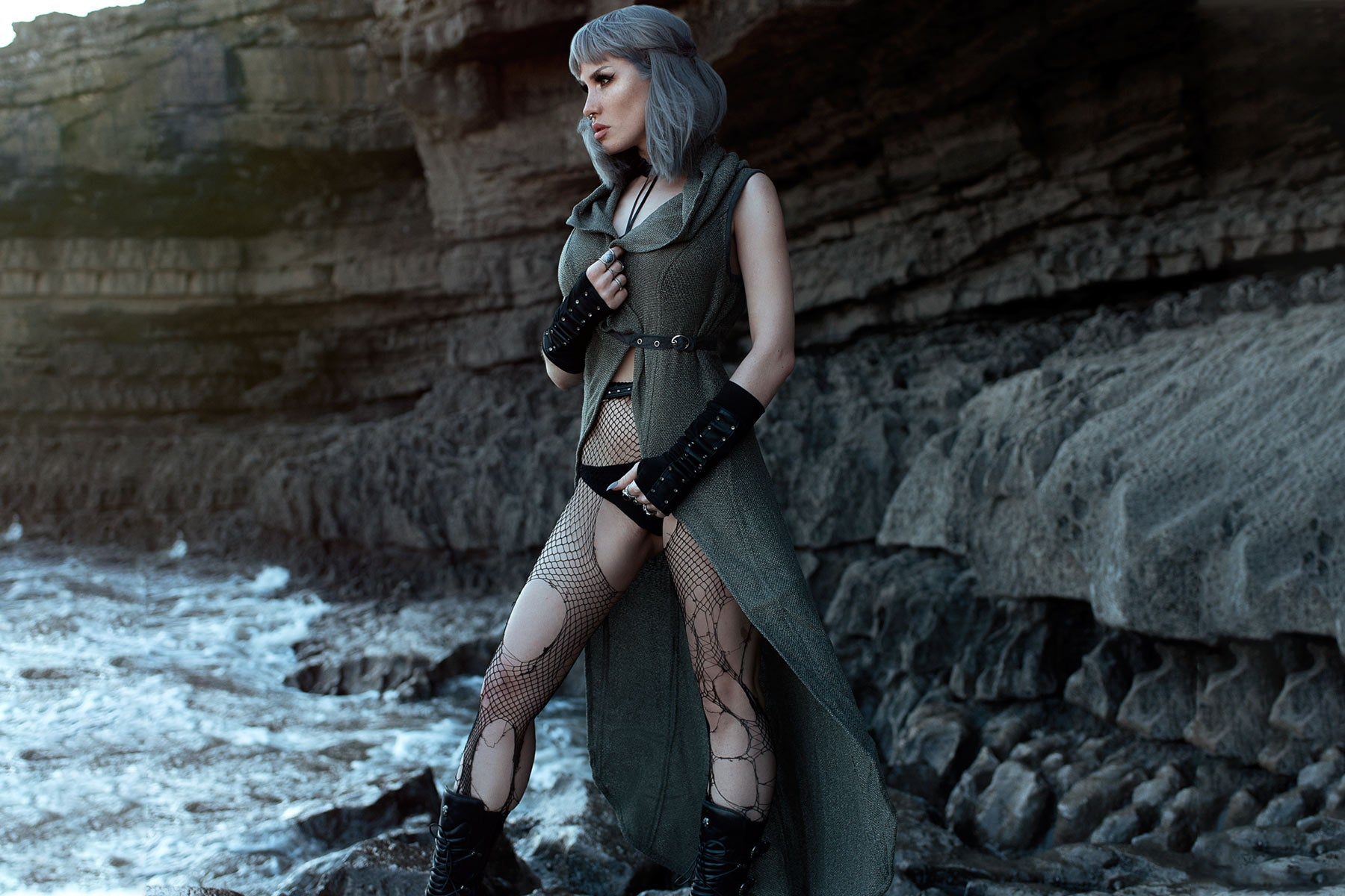 woman on a rocky beach wearing boho-chic gothic clothing by Alekai