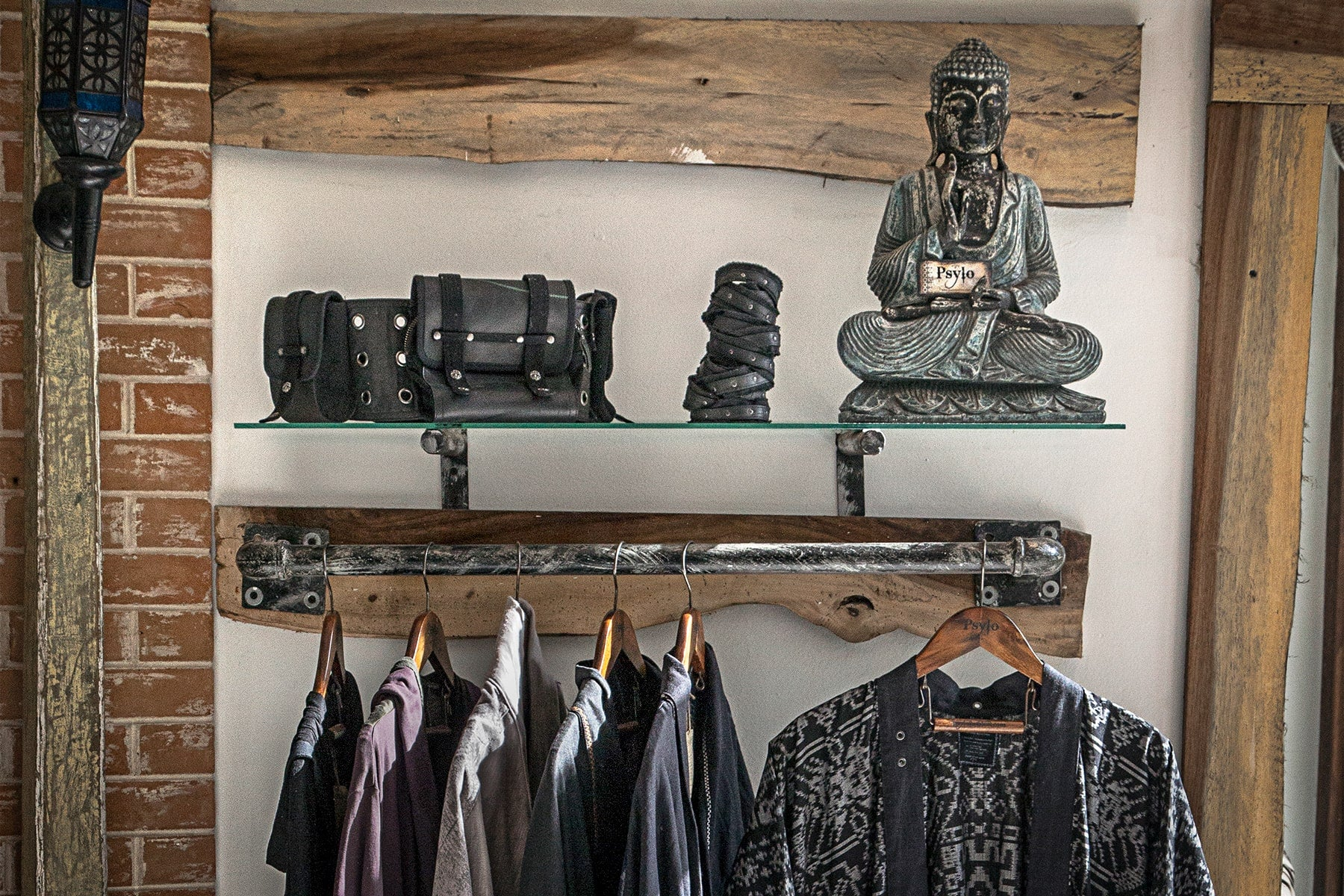 Psylo alternative streetwear hanging on a clothes rail with Buddha statue slow fashion guide