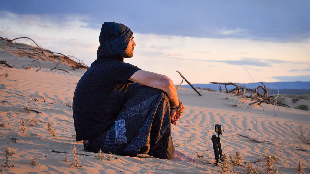 Max relaxing in the Gobi desert wearing Psylo clothing