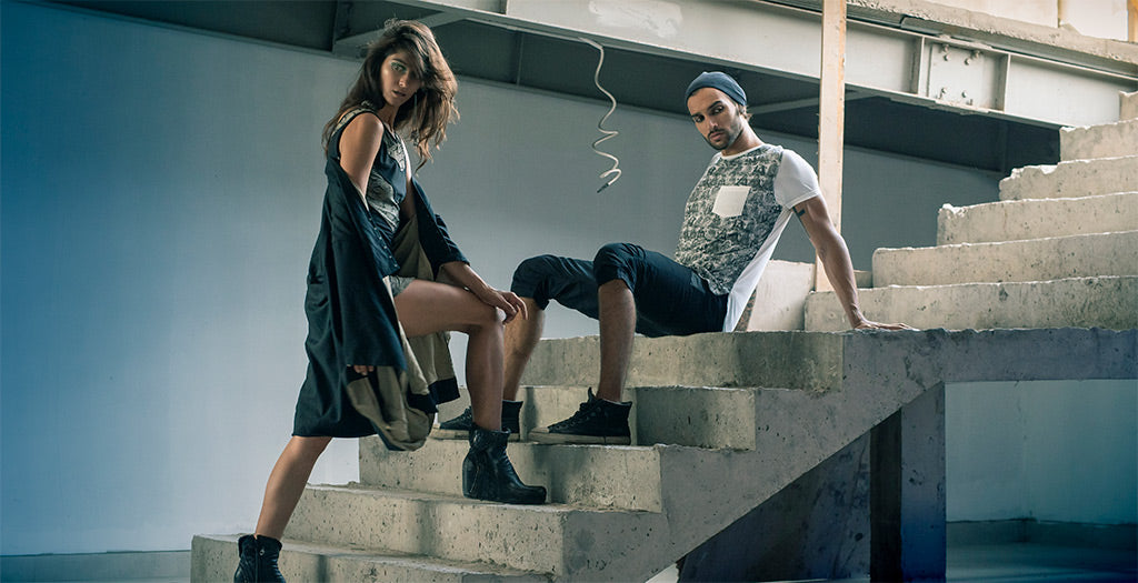 Woman standing and man sitting on stairs wearing Psylo fashion ethical streetwear