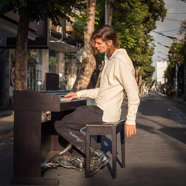 A guy playing piano in middle of empty street wearing psylo fashion unisex clothes