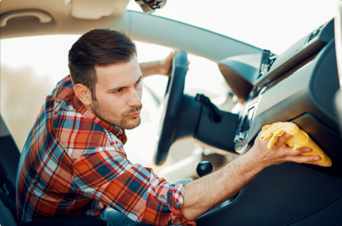 Man cleaning the console of his car with a microfiber towel