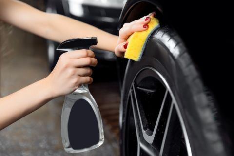 person using wheel cleaner spray to shine their tires
