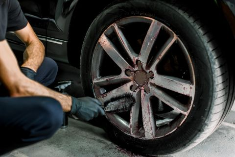 person using wheel cleaning brush to clean dirt from aluminum rims