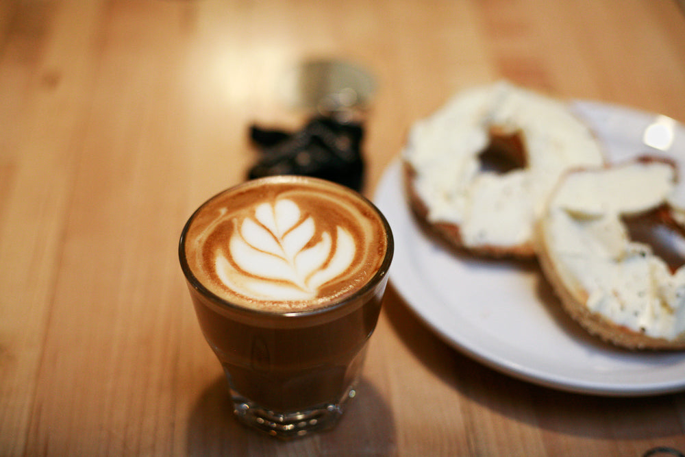 coffee with latte art and a bagel with cream cheese