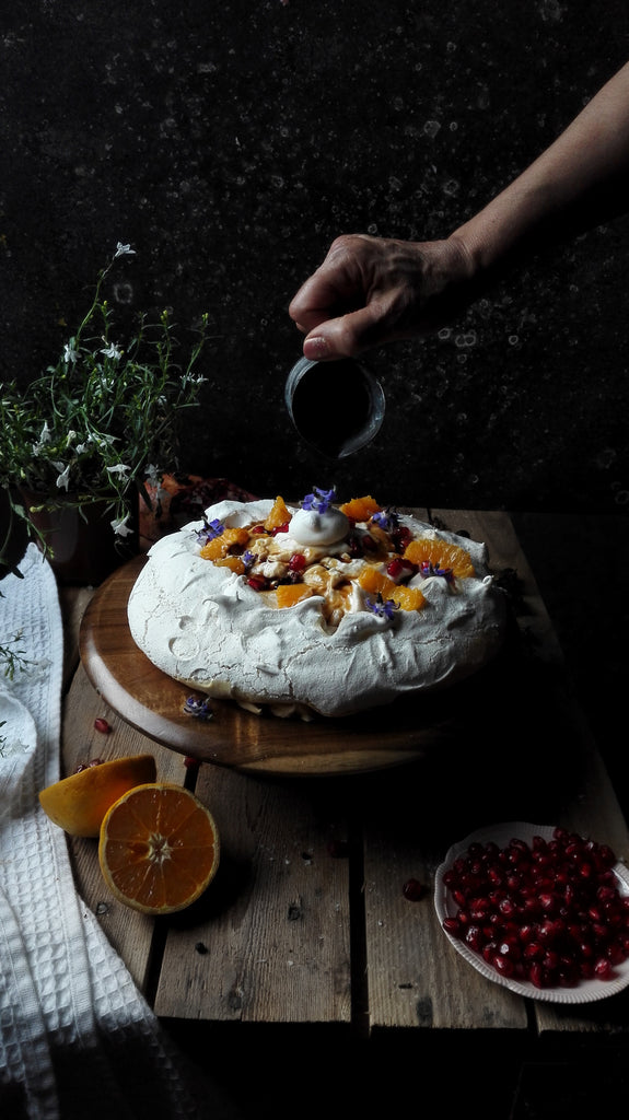 Vegan Pavlova with orange blossom cream cheese and pomegranate molasses drizzle