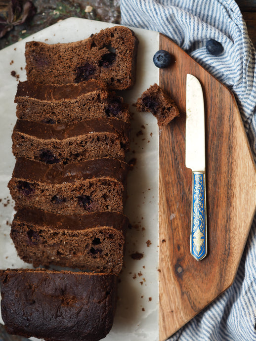 Nine Tea Cups Gluten Free Dairy Free Spiced Blueberry Breakfast Bread Sliced on an octagonal marble chopping board, with fresh blueberries, placed on a striped cloth and next to a blue enamel bread knife