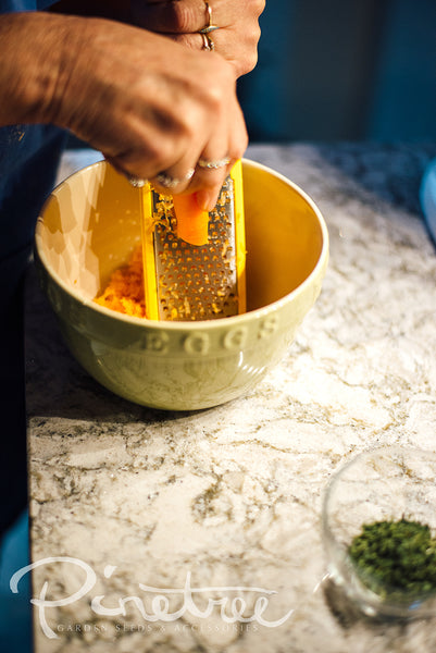 hands grating carrot into a bowl on a kitchen  countertop