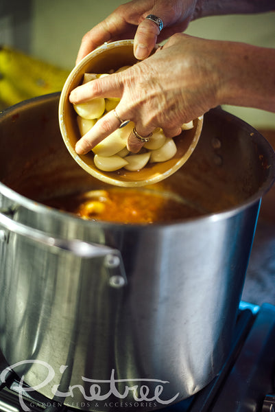 hands pouring garlic from a bowl into sauce in a pot