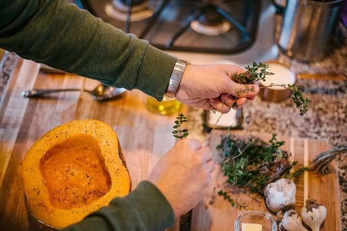 hands with fresh thyme adding to a pumpkin half on a cutting board in kitchen
