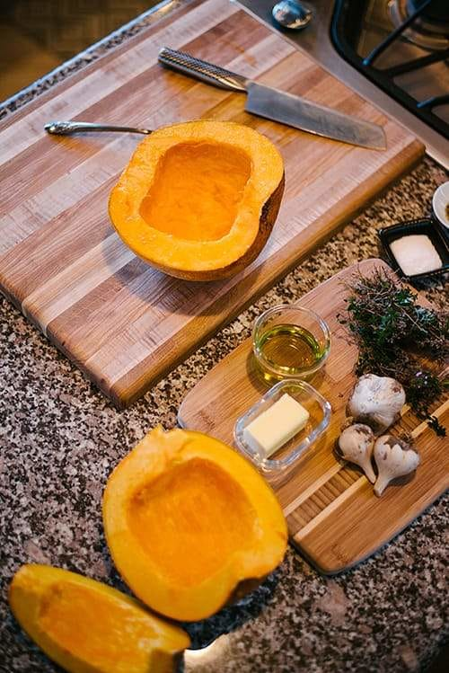 pumpkins cut in half on countertop with knife, spoon, spices, herbs, garlic, butter, on a cutting board