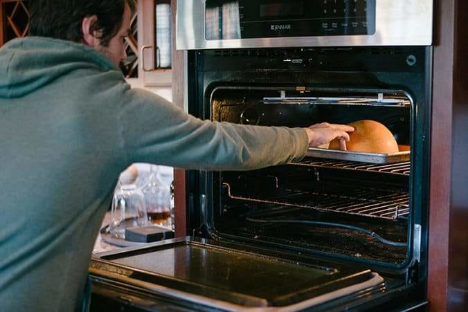 man placing baking pan with pumpkin half into oven
